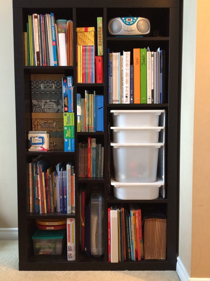 Homeschooling shelf with books and bins