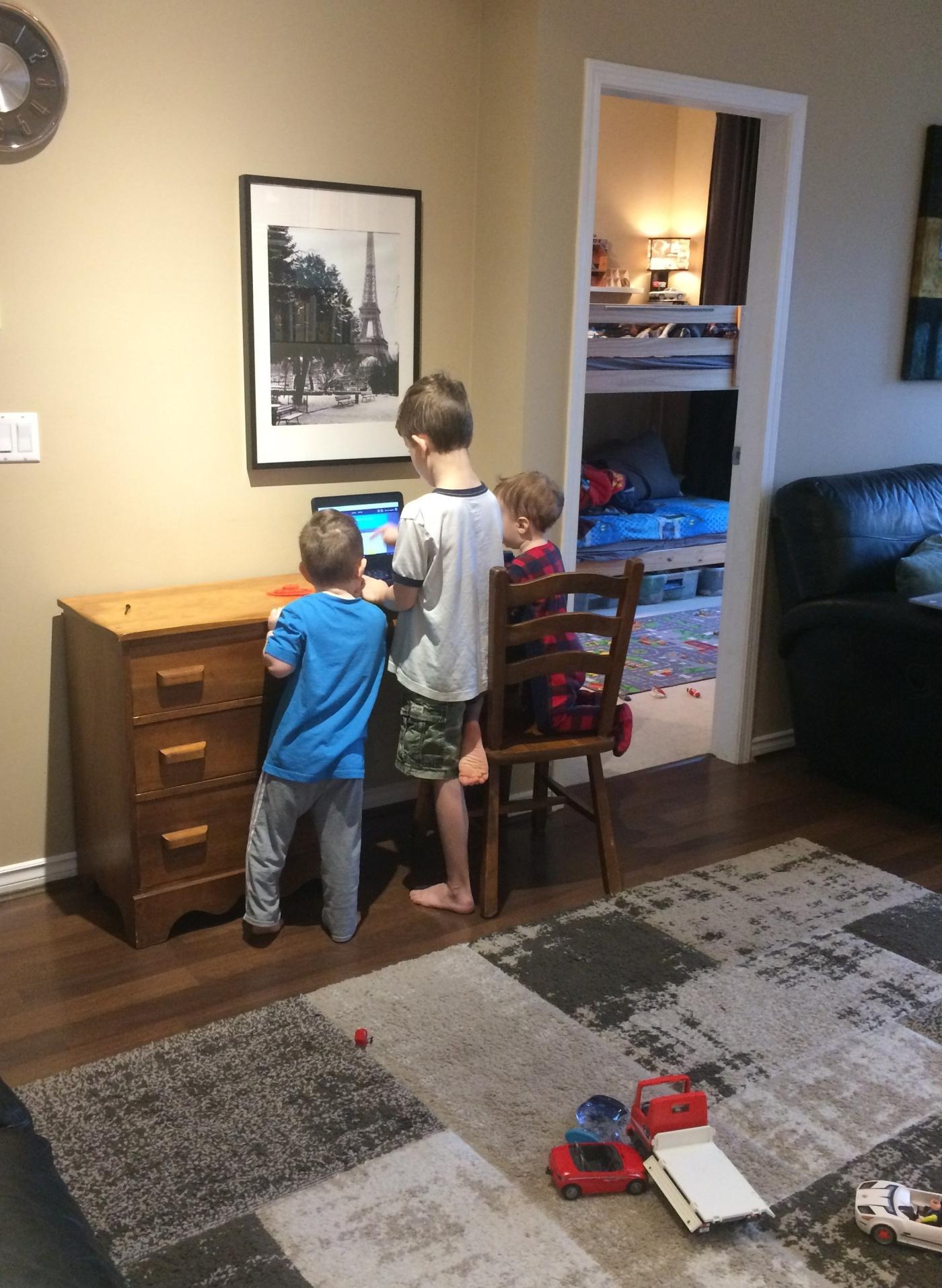 Three boys homeschooling at living room desk