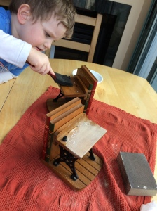 Little boy sanding and painting oil onto old school-desk bookends.