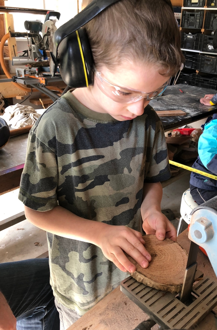 Boy wearing safety glasses and ear protection sanding a piece of wood on electric saw.